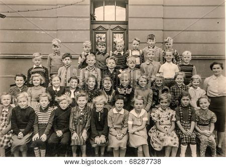 GERMANY, CIRCA 1953 - Vintage photo of group of schoolmates and teacher posing in front of their school