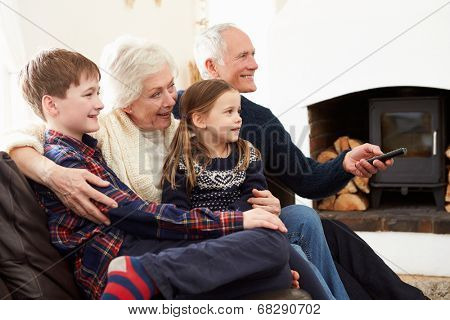 Grandparents Sitting On Sofa Watching TV With Grandchildren