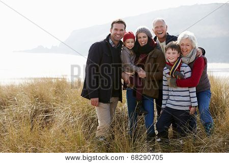 Multi Generation Family In Sand Dunes On Winter Beach