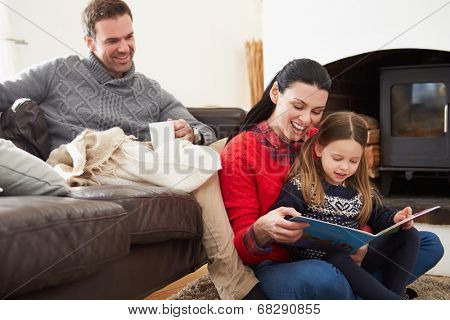 Family Relaxing Indoors And Reading Book