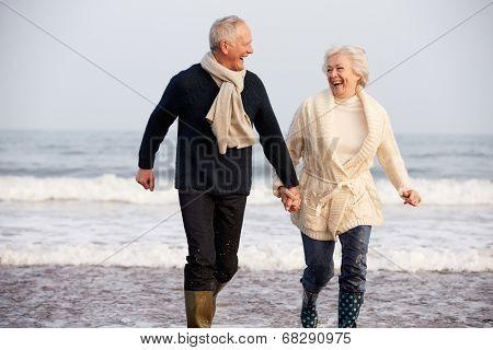 Senior Couple Running Along Winter Beach