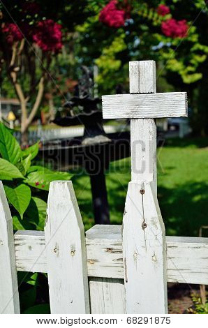 Wooden cross on picket fence