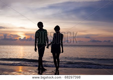 sunset silhouette of young couple in love at beach
