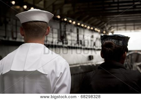 NEW YORK - MAY 22: Two sailors stand at the top of the ramp of the well deck aboard the amphibious dock landing ship USS Oak Hill (LSD 51) moored at Pier 92 for Fleet Week NY on May 22, 2014.