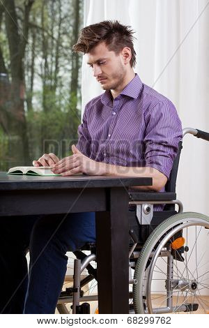 Disabled Man Reading A Book At Home