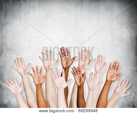 Group of human arms raised with concrete wall.