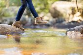stock photo of legs feet  - young woman hiking in mountain crossing stream - JPG