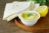 picture of chickpea  - traditional hummus dip of chickpea with pita bread on a wooden table