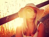 picture of shy woman  - a pretty woman sitting on steps at sunrise or sunset toned with an instagram like filter - JPG