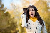 stock photo of jaw drop  - Amazed fashionable woman with mouth open looking surprised raising her glasses in autumn - JPG