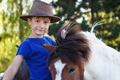 pic of breed horse  - Little boy with pony on farm horse therapy - JPG