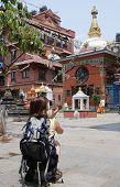 Tourist With Camera In Front Of Budhist Monastery poster