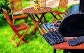 stock photo of bbq party  - Summer Party or Picnic Scene. BBQ Grill with BBQ tools garden furniture on the lawn in blurred background.