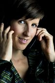 image of long distance  - Portrait of a young brunette friendly woman using headset with headphones and microphone for long-distance calls or customer service.