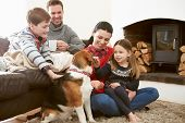 pic of indoor games  - Family Relaxing Indoors And Stroking Pet Dog - JPG