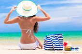 picture of beach hat  - back view of a woman with stripy bag and straw hat at tropical beach - JPG