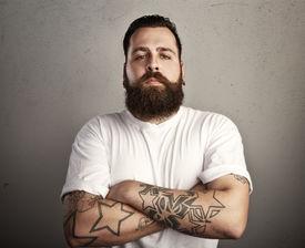 stock photo of hooligan  - Tattooed brutal bearded man wearing white t - JPG