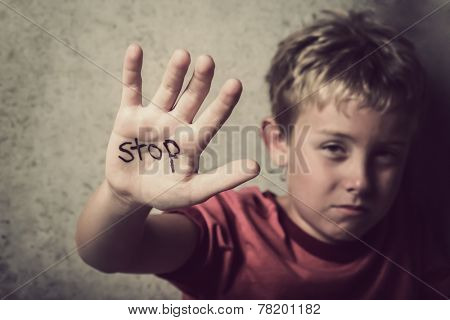 Scared boy with Stop written on his hand
