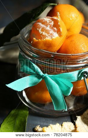 Juicy ripe tangerines with leaves on wooden table