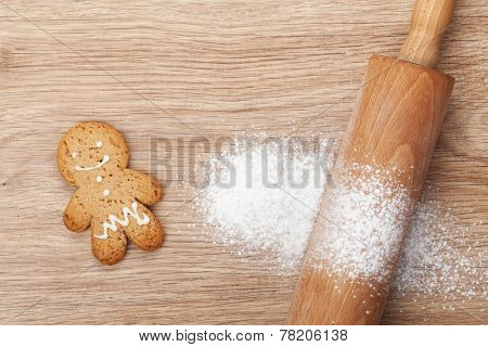 Rolling pin with flour and gingerbread cookie on wooden table. View from above