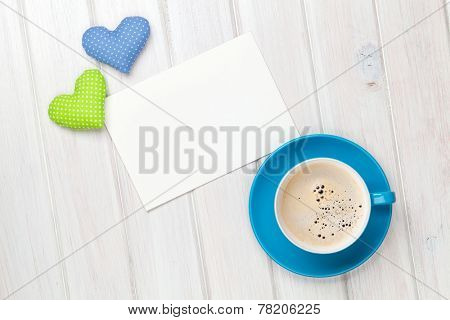 Valentines day toy heart, blank greeting card and coffee cup over wooden table background