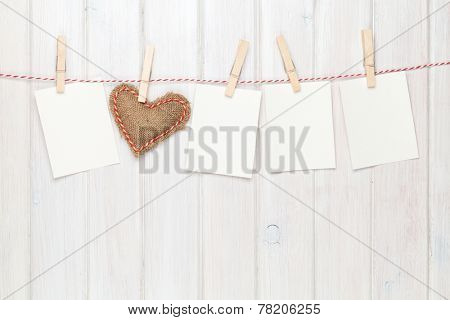 Photo frames and valentines toy heart over wooden background