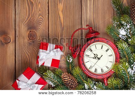 Christmas wooden background with clock, gift boxes, snow fir tree and copy space