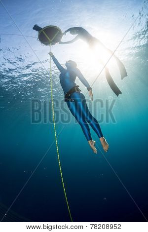 Free diver ascending along the rope