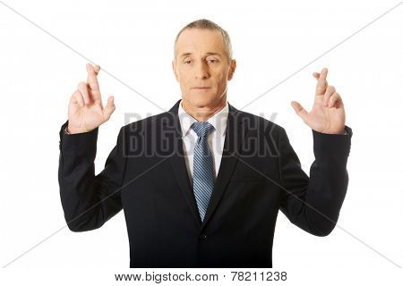 Businessman making a wish with fingers crossed.