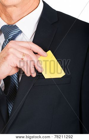 Businessman taking a yellow card from pocket.