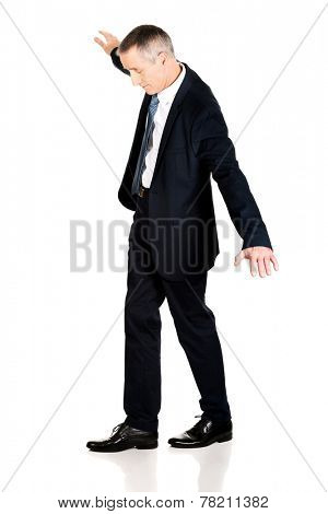Full length businessman walking carefully.