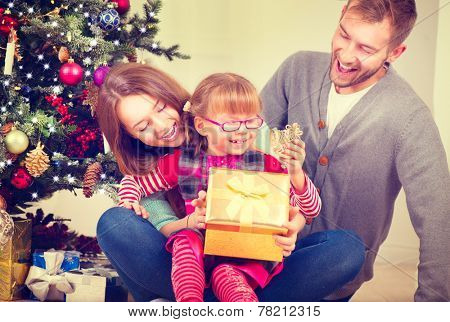 Christmas Family with little daughter opening Christmas gifts. Happy Smiling Parents and Child at Home Celebrating New Year. Christmas Tree. Christmas scene