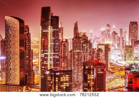 Beautiful background of Dubai at night, gorgeous cityscape over pink sky, many glowing lights of tall skyscrapers, luxury modern expensive architecture design