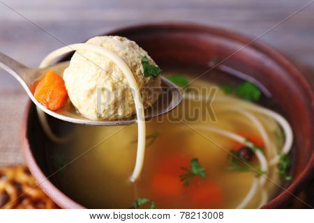 Meatball in spoon, close-up. Soup with meatballs and noodles in bowl on wooden background