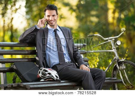 young man with his bicycle talking and resting in park