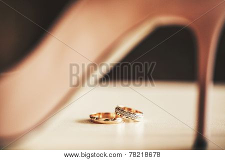 Wedding-ring Against The Background Of A Female Heel