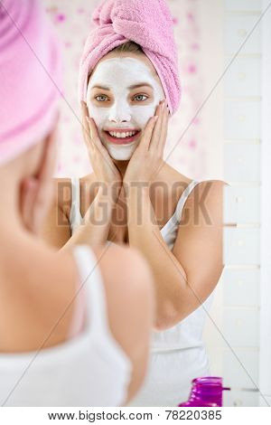 Young  woman applying facial cleansing mask, beauty treatments