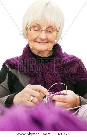 Portrait Of Active Senior Woman Knitting Against White
