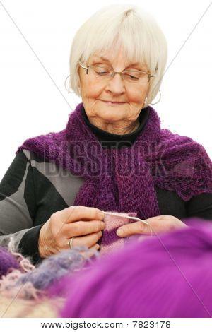 Portrait Of Elderly Woman Knitting Against White