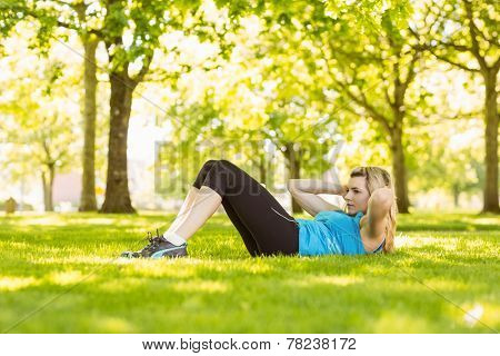Fit blonde doing sit ups in the park on a sunny day