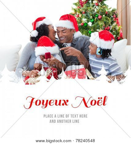 Happy family having fun with Christmas presents against joyeux noel