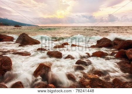 Big boulders and sea waves at sunrise
