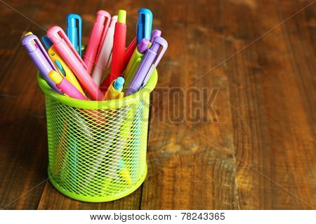 Metal holder with different pens on rustic wooden background