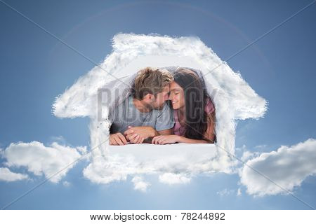 Cheerful couple head against head under the duvet against cloudy sky with sunshine
