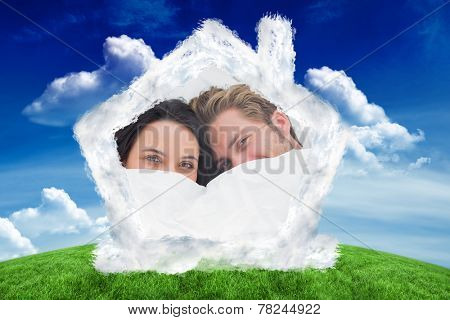 Couple hiding under the duvet against green field under blue sky