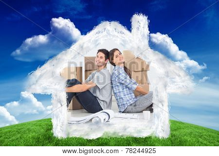 Couple sitting back-to-back against green field under blue sky