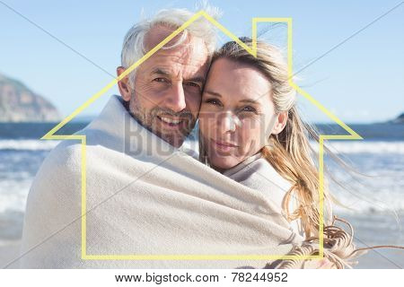 Smiling couple wrapped up in blanket on the beach against house outline