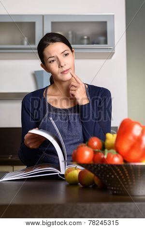 Thoughtful Woman Reading Recipe Book At The Kitchen Counter