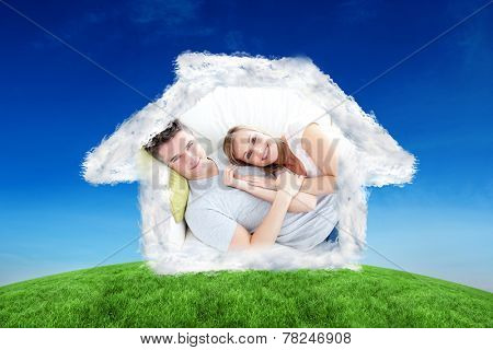Caress young couple lying together on the sofa in the livingroom against green hill under blue sky