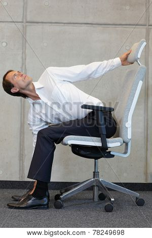 yoga with arm chair in office - business man exercising